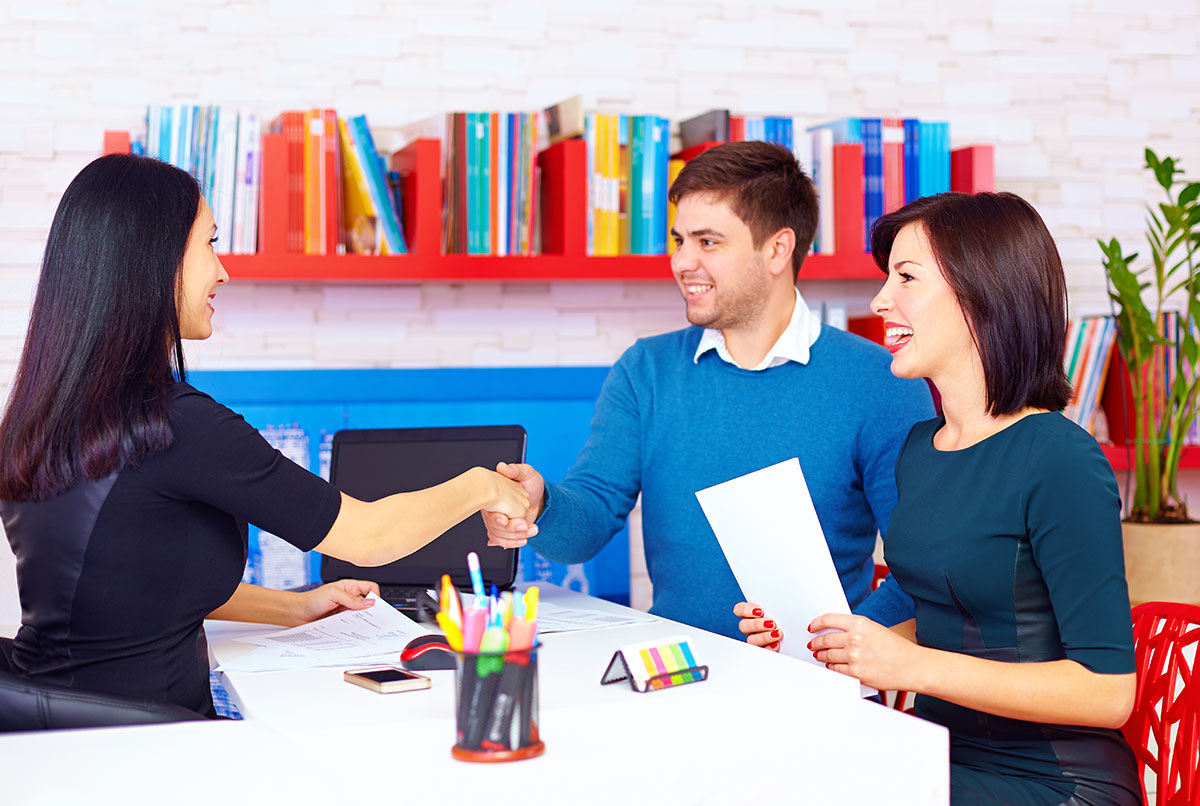 Designer at her office shaking a couples hands