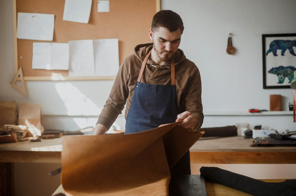 Craftsman working in his leather shop